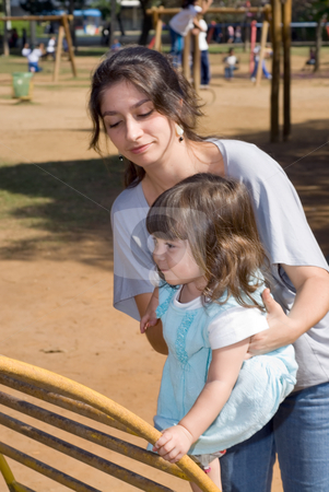 Mother and Daughter stock photo, Attractive mother helping her young daughter climb up a set of bars at the park. by Orange Line Media