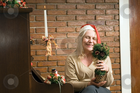 A Woman with Christmas decoration by a piano stock photo, A women holding a Christmas decoration sitting by a piano with Christmas candles. by Orange Line Media