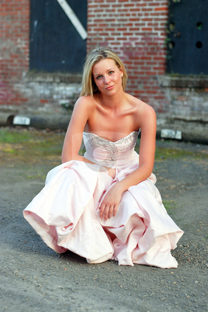 Bridesmaid Crouched in Front of Brick Wall - Vertical stock photo, Vertically framed outdoor shot of an attractive bridesmaid crouching down in front of red brick wall. by Orange Line Media