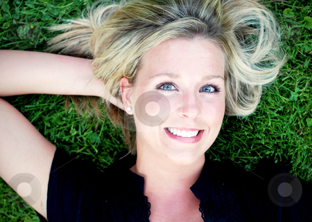 Cute Blond on the Grass stock photo, Attractive blond woman lying on a lush green lawn smiling at the camera. Horizontally framed close-up shot. by Orange Line Media