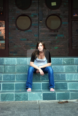 Cute Brunette stock photo, Young attractive brunette sitting comfortably on stone steps in the city. Vertically framed wide-angle shot. She is smiling and casually dressed. by Orange Line Media