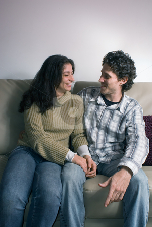 Loving Couple stock photo, Loving couple sitting on the couch and gazing deeply at each other. Vertically framed shot. by Orange Line Media