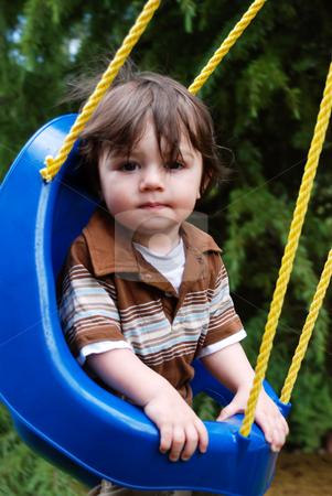Cute Boy in a Swing stock photo, Cute little boy in a kids swing looking straight at the camera. Vertically framed shot. by Orange Line Media