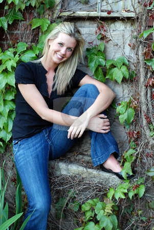 Attractive Blond Woman stock photo, Attractive young blond woman casually dressed smiling at the camera sitting by an ivy covered stone and brick wall by Orange Line Media
