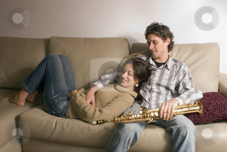 Couple Lying on the Couch stock photo, Attractive couple relaxing together on their living room couch. She is lying in his lap and he is a musician holding a saxophone. by Orange Line Media