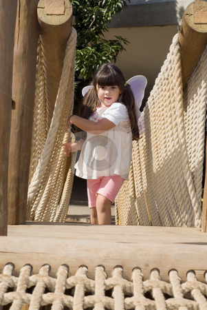 Cute Girl stock photo, Adorable young girl climbing gingerly up a rope bridge. Vertically framed shot. by Orange Line Media