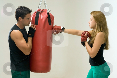 Woman Boxing with Trainer stock photo, Attractive woman working out with boxing gloves and a heavy punching bag with her trainer. by Orange Line Media