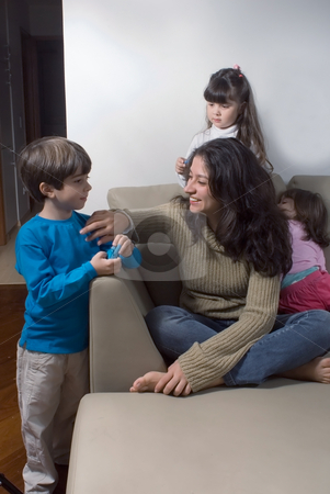 Mother and Children stock photo, Attractive mother and her children hanging out together in their living room by Orange Line Media