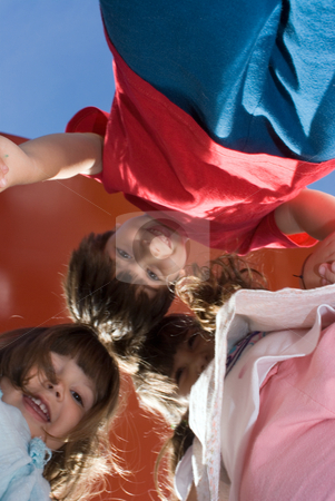 Three Kid Huddled Together Looking Down at Camera stock photo, Vertically framed outdoor shot of a two cute young girls and one young boy huddled together looking down at the camera on a sunny day. by Orange Line Media