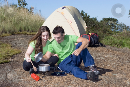 Couple on a Camping Trip - Horizontal stock photo, Attractive young couple cooking a meal while on a camping trip. Horizontally framed shot set against a clear blue sky by Orange Line Media