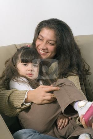 A Smiling Mother Cuddling Her Daughter stock photo, A smiling mother cuddling her daughter on a sofa. by Orange Line Media
