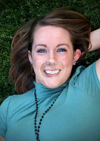 Teen Lying on Grass Looking Up stock photo, Vertically framed outdoor headshot of a teenage girl lying on grass looking up at the camera. by Orange Line Media