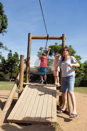 Family Fun stock photo, Attractive young family and their kids playing at the park together. The son is about to launch himself on a zip-line by Orange Line Media