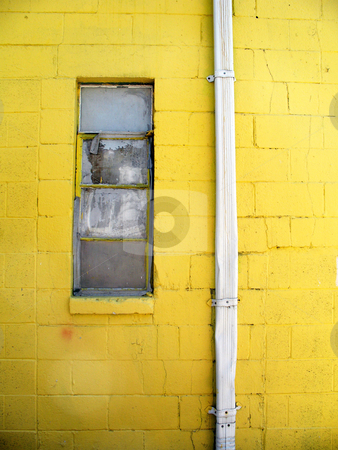 Broken Window stock photo, Broken window next to a drainpipe framed by the yellow wall of an abandoned building by Orange Line Media