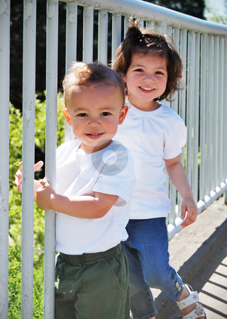 Brother and Sister stock photo, Cute young brother and sister playing together by a guardrail on a sunny day. Vertically framed shot. by Orange Line Media
