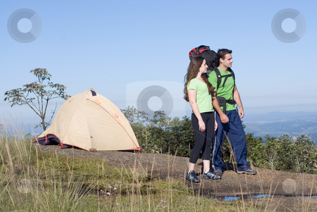 Talking in the View - Horizontal stock photo, A young attractive backpacking couple standing on a rock outcropping, taking in the sky and mountian views.  The shot is horizontally framed. by Orange Line Media