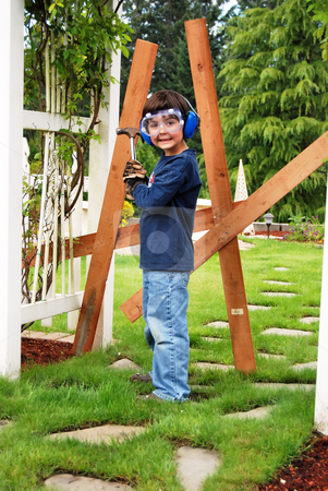 Young Handyman stock photo, Little boy wearing protective eyewear and toting a hammer ready to go to work on his latest construction project. Vertically framed shot. by Orange Line Media