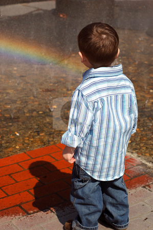 Young Boy Looking into Fountain stock photo, Young boy looking  into a fountain that has rainbow in it, with his back to the camera, wearing blue button-up shirt. by Orange Line Media