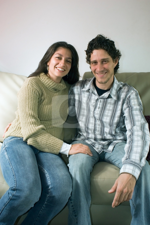 Couple on the Couch - Vertical stock photo, Attractive couple hugging each other and smiling while sitting on their living room couch by Orange Line Media