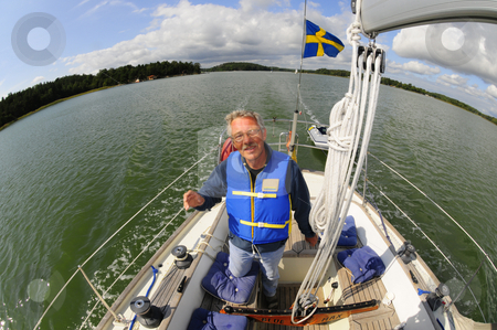 Happy sailor stock photo, Happy sailor navigating his boat in the archipelago by Magnus Johansson