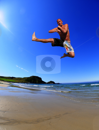 Beach fighter stock photo, Man practicing martial art on the beach by Magnus Johansson