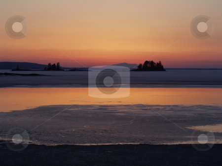 Winter sunset stock photo, Sunset over a frozen lake by Ingvar Bjork