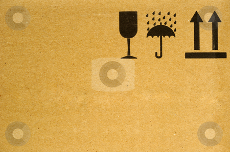 Handle with care stock photo, The symbols 'fragile', 'keep dry' and 'this way up' on the side of a cardboard box. Space for text on the cardboard. by Alistair Scott