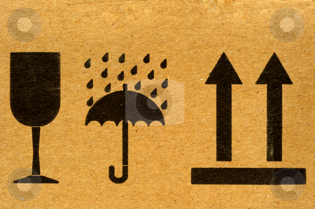 Handle with care stock photo, The symbols 'fragile', 'keep dry' and 'this way up' on cardboard. by Alistair Scott