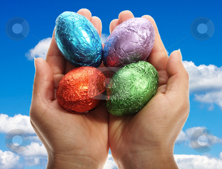 Holding four chocolate Easter eggs stock photo, Two hands holding four chocolate Easter eggs isolated with area for text by Christopher Meder