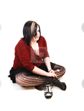 Girl sitting on floor. stock photo, Young big woman sitting on the floor, putting on her shoes and the pantyhose is all ripped up. by Horst Petzold