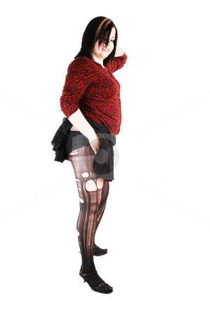 Girl with ripped pantyhose. stock photo, Young woman standing in the studio with a red blouse and black short skirt shooing her panties and the ripped pantyhose. by Horst Petzold