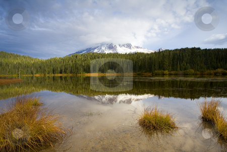 Holding back the Tempest stock photo, A gathering storm fanning out over the top of Mt. Rainier on an Autumn morning by Mike Dawson