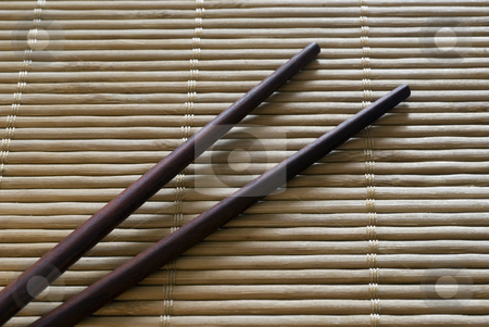 Asian Cuisine stock photo, Chopsticks on a bamboo roll placemat by Stephen Gibson