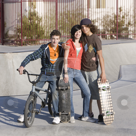 Three teens at skatepark stock photo, Three kids hang out at the skatepark by Rick Becker-Leckrone