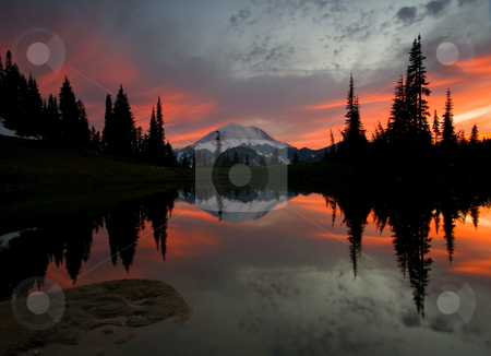 Fire in the Sky stock photo, Mt. Rainier reflects in the still waters of a small alpine lake at sunset. by Mike Dawson