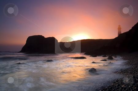 From Light to Light stock photo, The sun sets on a foggy evening behing the Yaquina Head Lighthouse on the ORegon Coast by Mike Dawson