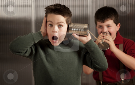 Little boy getting shocking message on tin can phone stock photo, Little boy getting shocking message from friend on tin can phone by Scott Griessel