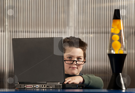 Boy working on a laptop computer stock photo, Cute young boy dressed as an adult working on a laptop computer by Scott Griessel