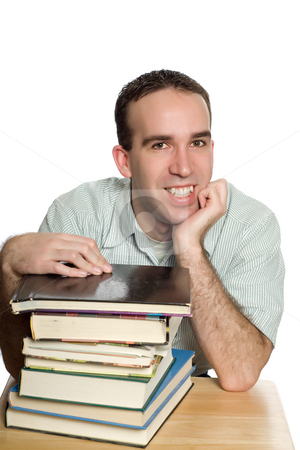 Smiling Student stock photo, A smiling student sitting at his desk with a pile of books, isolated against a white background by Richard Nelson