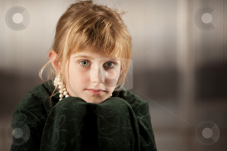 Cute young girl with big eyes stock photo, Cute young girl with big eyes in dress-up clothes chin on knees by Scott Griessel