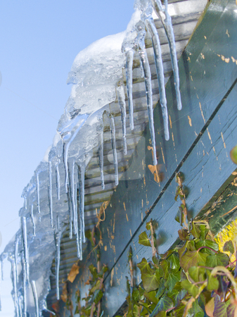 Ice hanging from a roof stock photo, Ice hanging down from a green  roof by Phillip Dyhr Hobbs
