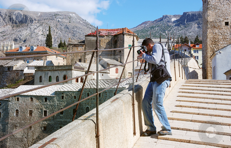Photographer shooting stock photo, A photographer shooting from the Old Bridge in Mostar by Ivan Paunovic