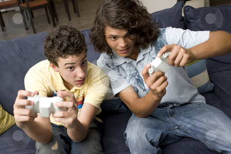 Two guys play videogames stock photo, To guys play videogames on a couch by Rick Becker-Leckrone