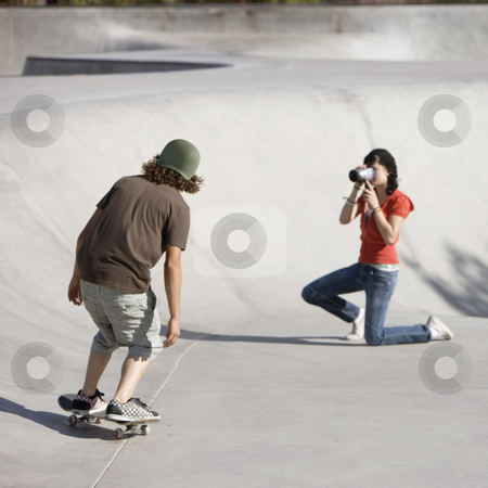 Videotaping skateboard action stock photo, Boy dies tricks at the skateboard park as girl videotapes by Rick Becker-Leckrone