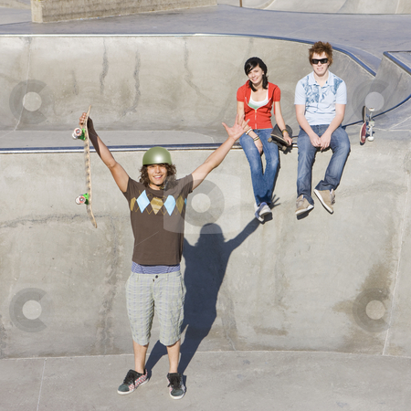 Triumphant skateboarder stock photo, Triumphant skateboarder gestures in front of his friends by Rick Becker-Leckrone