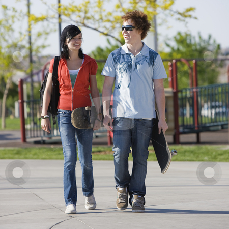 Teens couple walks stock photo, Two kids walk home through a park by Rick Becker-Leckrone