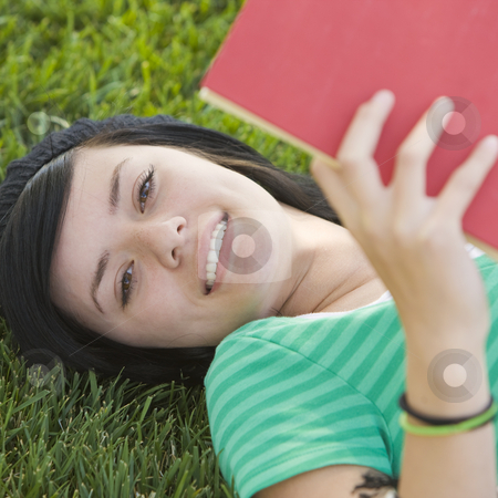Teen studies with book in grass stock photo, Happy teen studies with book in the grass by Rick Becker-Leckrone