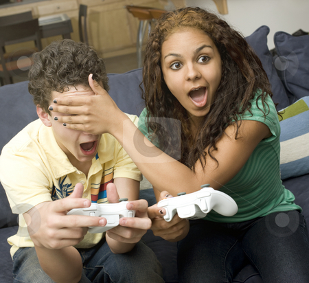 Teens play video games on couch stock photo, Teen boy and girl joke around while playing video games on a couch by Rick Becker-Leckrone