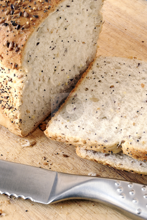Sliced seeded bread stock photo, Sliced of fresh seeded bread on a wooden board with bread knife by Paul Turner