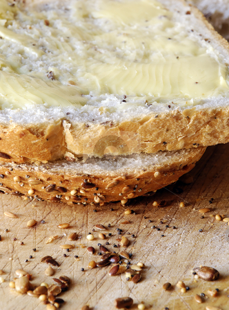 Bread and butter stock photo, Slices of fresh seeded bread, spread with butter by Paul Turner